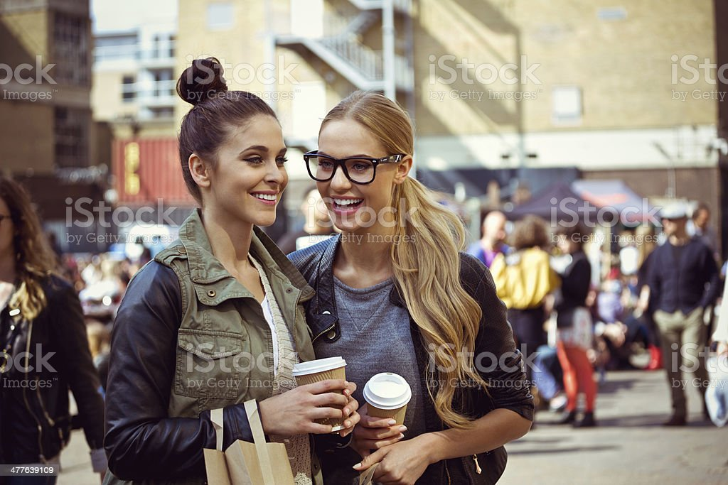 Friends laughing outdoors Two young women standing on the city street, holding take coffee in hands and having fun. 20-24 Years Stock Photo