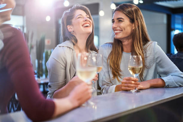 Friends laughing while enjoying drinks in bar stock photo