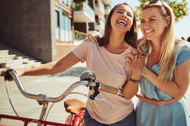 freunde lachen bei einem spaziergang mit ihrem fahrrad in der stadt - freundin stock-fotos und bilder