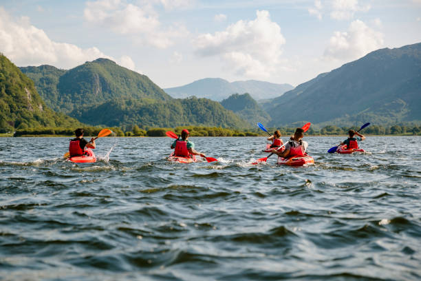 Friends Learning To Kayak Friends learning to kayak on Derwent Water in The Lakes District in Cumbria cumbria stock pictures, royalty-free photos & images