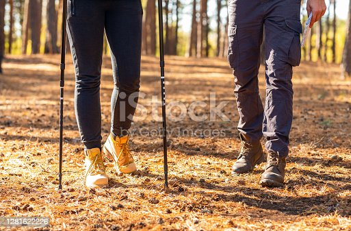Two friends legs walking by autumn forest, closeup