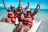 istock Friends Lifting Their Arms Up During Pedal Boat Fun On Sea 1218711223