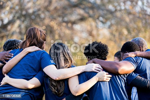 Diverse group of friends cleanup a park during a charity event. They are standing with their arms around one another.