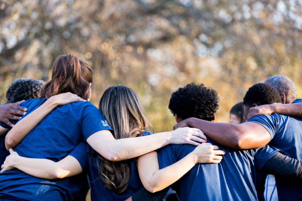 Friends linking arms in unity Diverse group of friends cleanup a park during a charity event. They are standing with their arms around one another. unity stock pictures, royalty-free photos & images