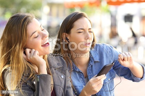 istock Friends listening music on line and singing 657424394