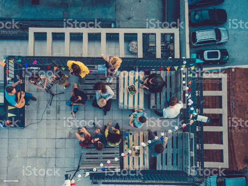 Friends listening to a music band on the rooftop stock photo