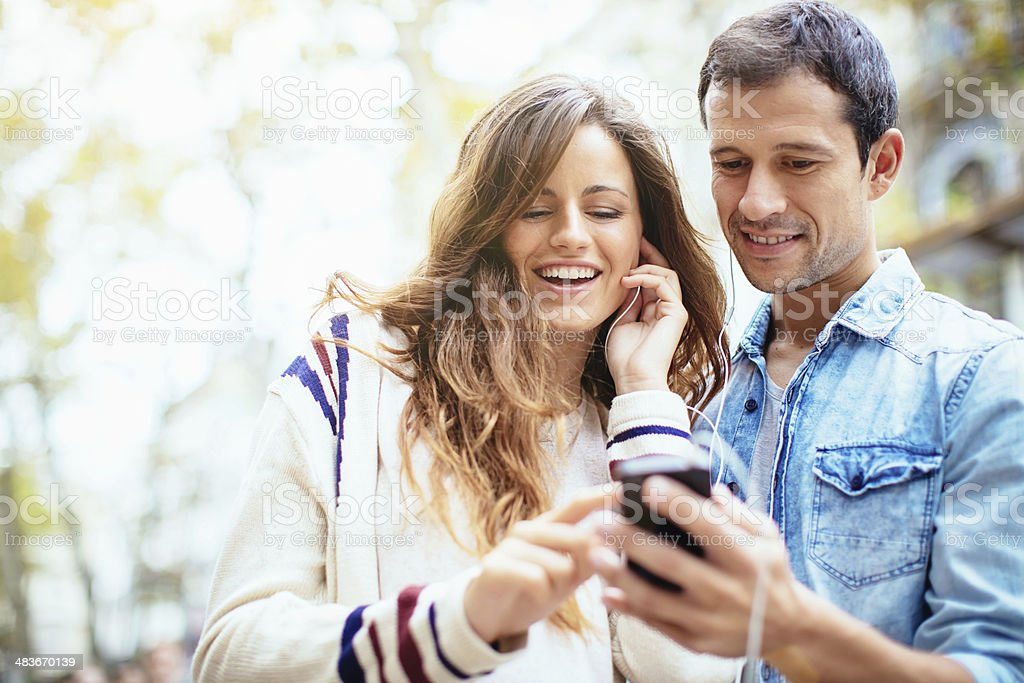 Friends Listening to Music Happy couple standing together outdoors in the sunlight, listening to music with mobile phone and earphones. Adult Stock Photo
