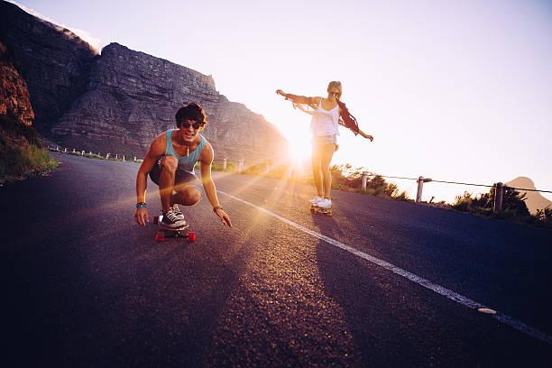 Friends longboard skating on road sunset stock photo