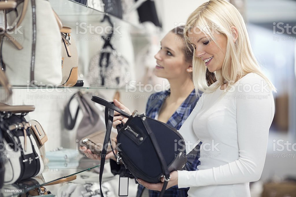 friends looking and buying  handbags   in department store royalty-free stock photo