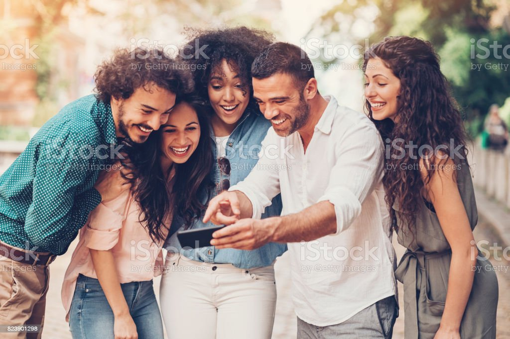 Friends looking at a smart phone stock photo