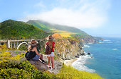 Sisters on vacation. Girls  relaxing, looking at beautiful summer mountains landscape, on hiking trip   Bixby Creek Bridge,  famous bridge on highway 1 in California over Pacific Ocean. Big Sur, California, USA