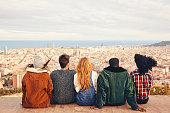 Rear view of friends sitting on building terrace. Males and females are looking at cityscape and sea. They are wearing casuals.