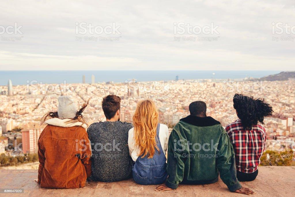Amigos buscando en la ciudad mientras está sentado en la terraza - foto de stock