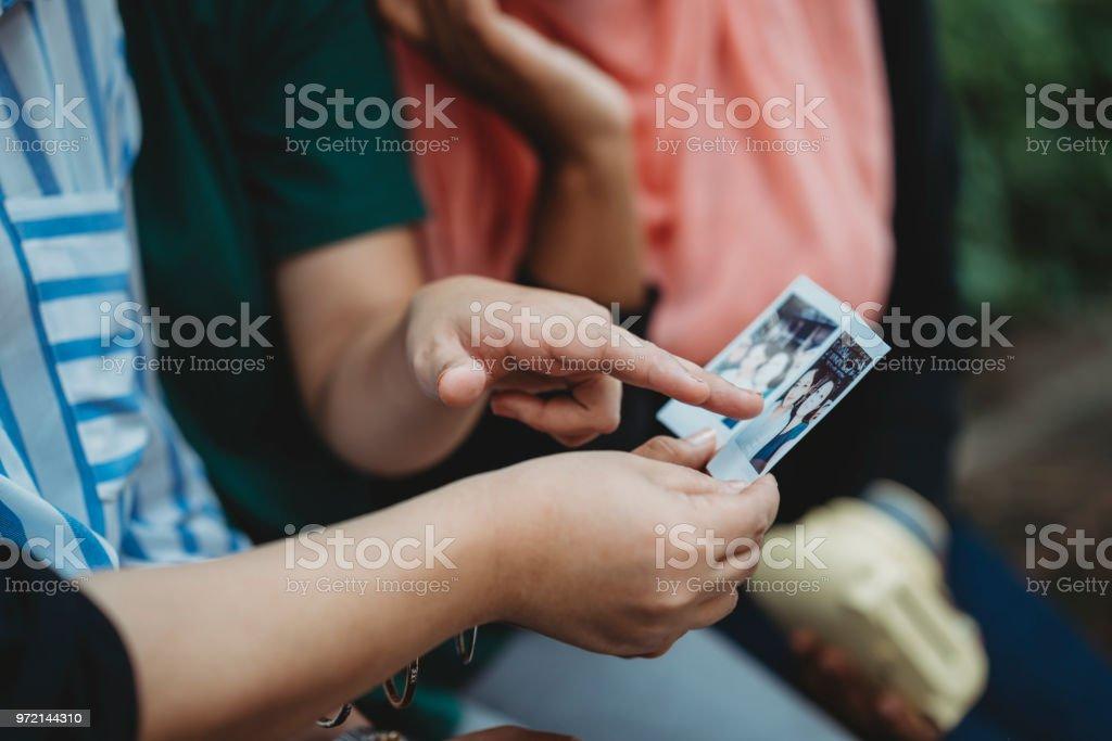 Amigos olhando instante Imprimir foto juntos - foto de acervo