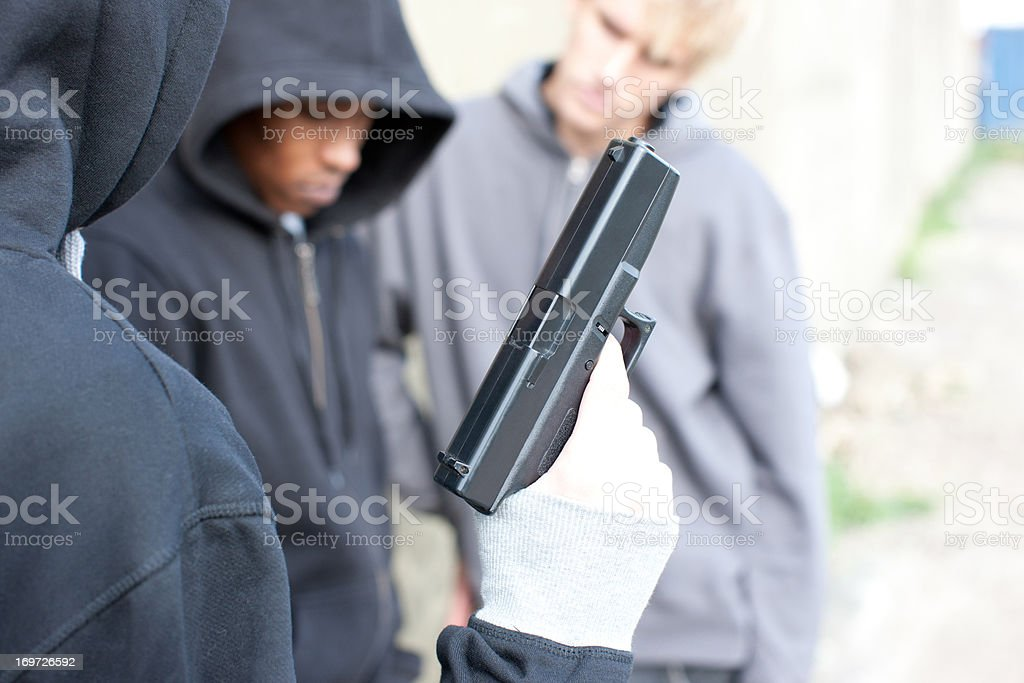 Friends looking at man holding gun stock photo