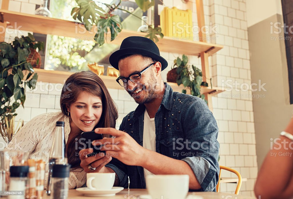 Friends looking at mobile phone while sitting in cafe - foto de stock
