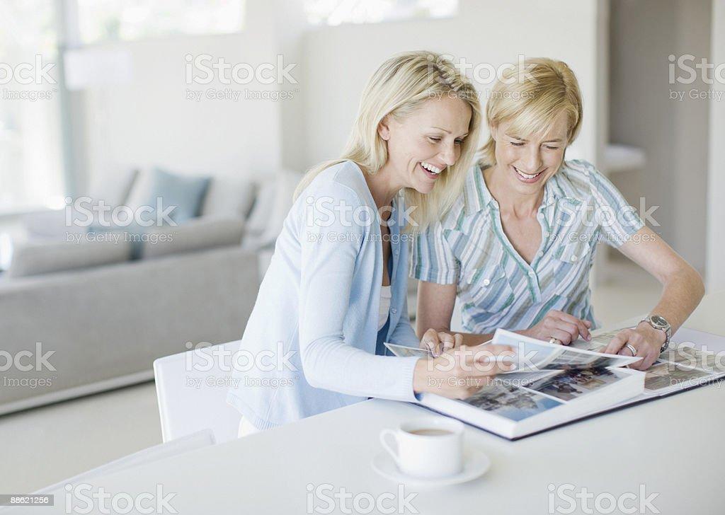 Amigos mirando juntos álbum de fotos - foto de stock