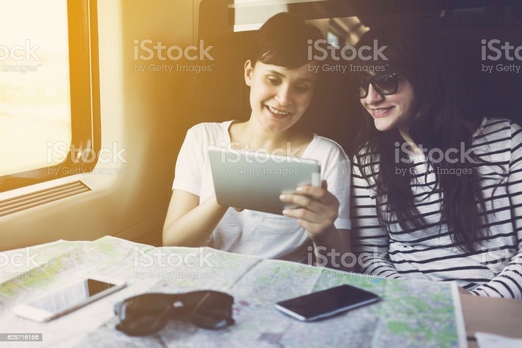 Friends looking at tablet pc, travelling in a train stock photo