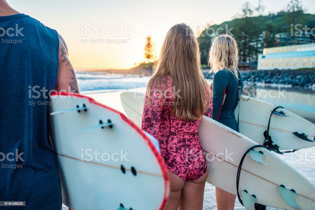Friends looking at the sunset and holding surfboards stock photo