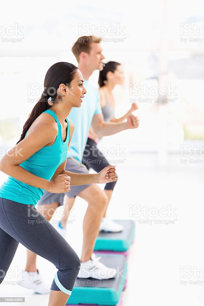Friends Looking Away While Doing Step Aerobics In Gym stock photo