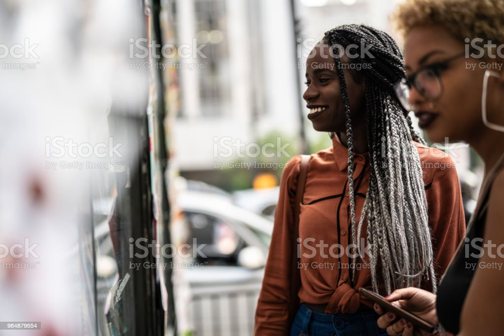 Friends Looking for Newspaper on Store royalty-free stock photo