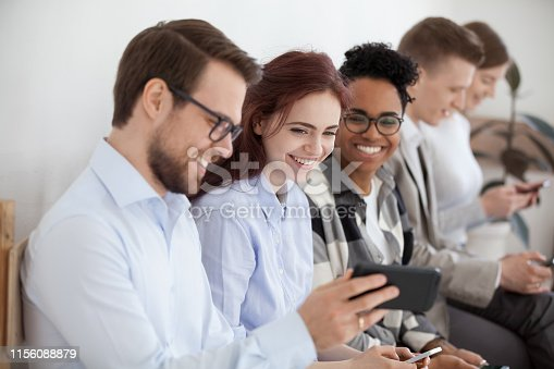 Diverse young businesspeople students friends sitting together in chairs in queue using mobile phones wait job interview or examination. Male showing funny video people laughing, positive emotions