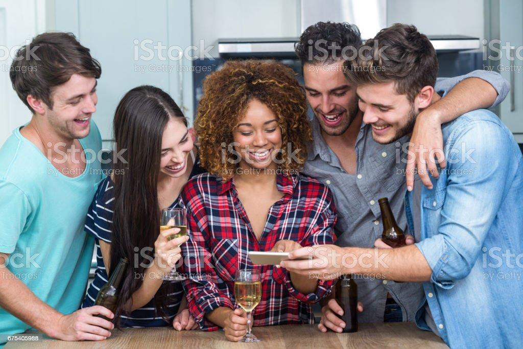 Amis à la recherche de téléphone mobile lorsque vous êtes debout par table photo libre de droits
