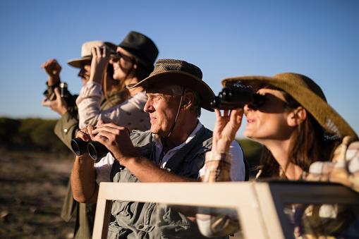 Friends looking through binoculars during safari vacation