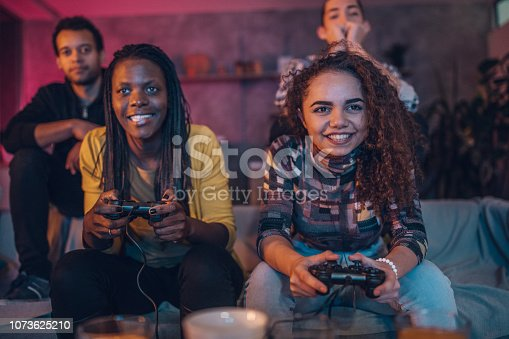 Group of multi ethnic people, friends sitting at home, playing video games.