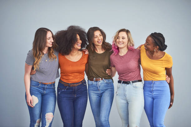 Friends make the world a happier place Studio shot of a group of attractive young women embracing against a gray background women stock pictures, royalty-free photos & images