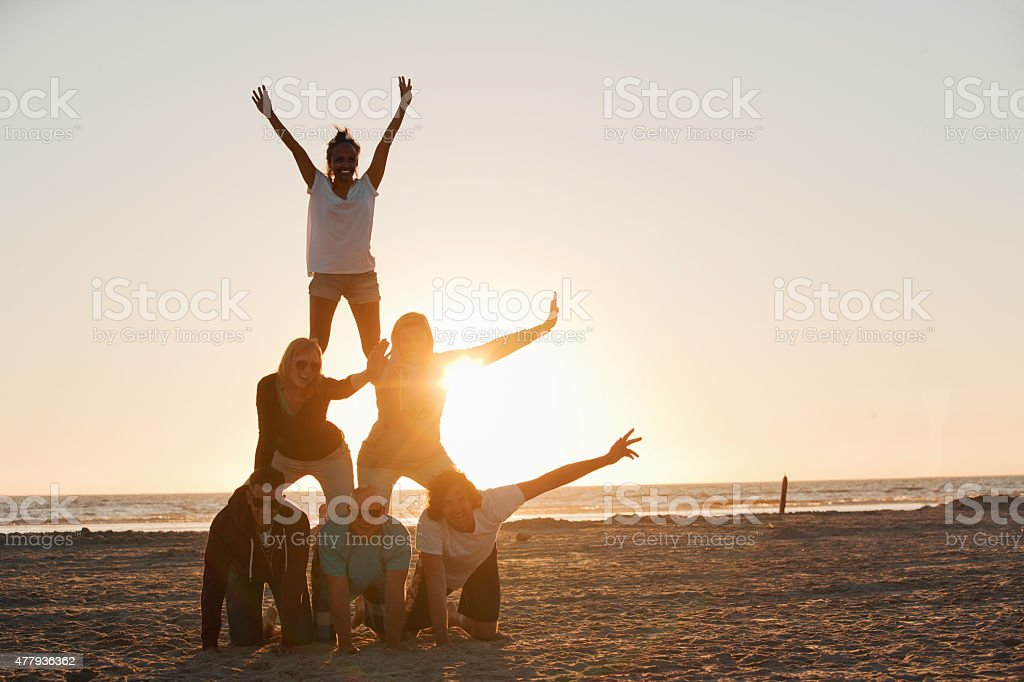Friends making a pyramid on the beach of St.Peter-Ording stock photo