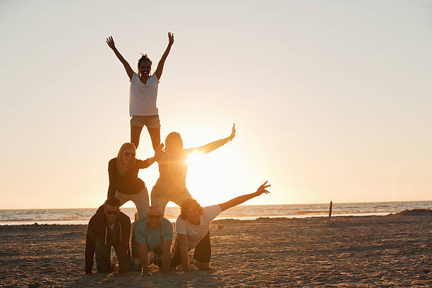 friends making a pyramid on the beach of st.peter-ording - pyramid stock photos and pictures