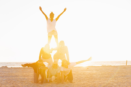 Friends making a pyramid on the beach of St.Peter-Ording