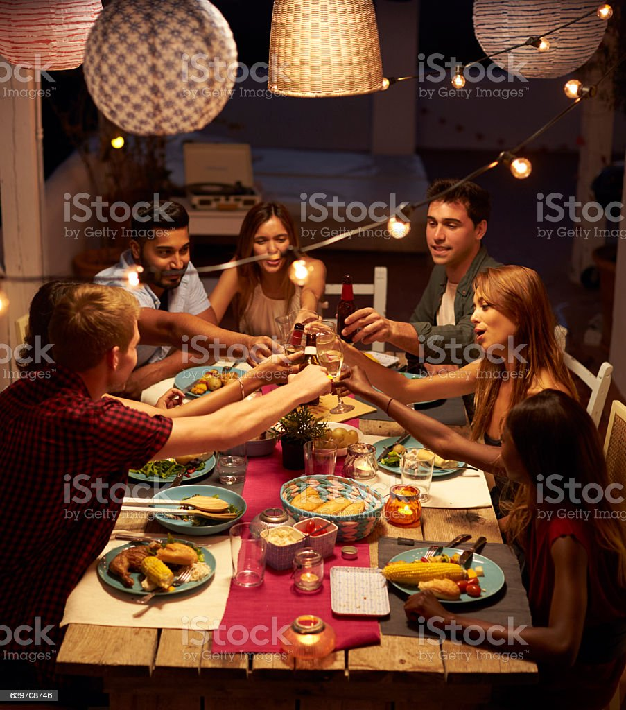 Friends making a toast at a patio dinner party, vertical stock photo