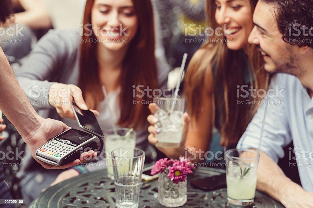 Freunde, die mit Smartphones Kontaktloses bezahlen – Foto