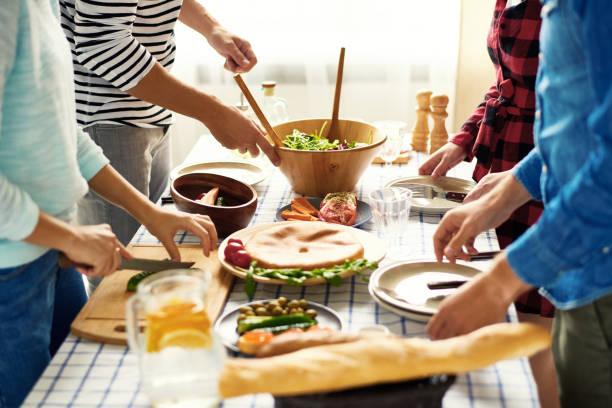 amis, faire un dîner ensemble - repas amis photos et images de collection