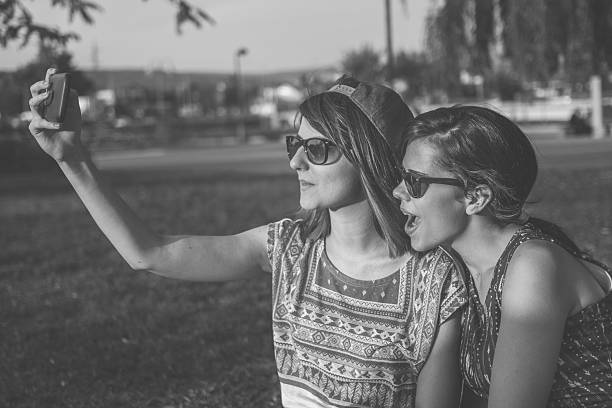 friends making selfie. two beautiful young women making selfie - beautiful college girl pics stock photos and pictures