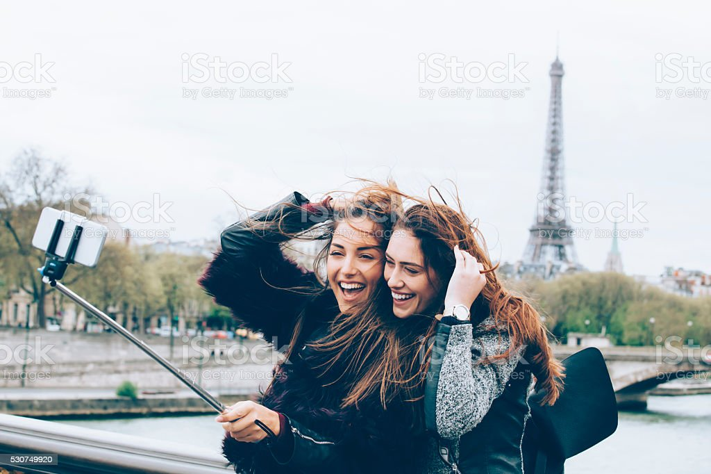 Friends making selfie with monopod in front of Eiffel tower stock photo
