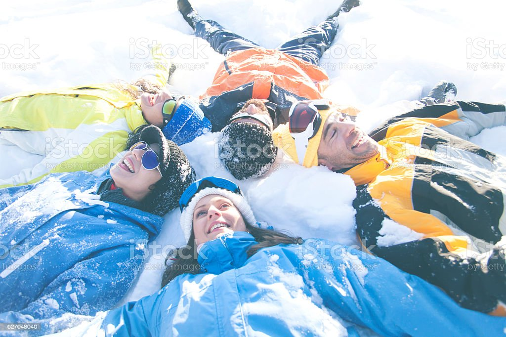 Friends making snow angels stock photo
