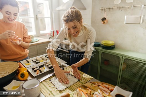 Photo of two young women making sushi together in the kitchen.