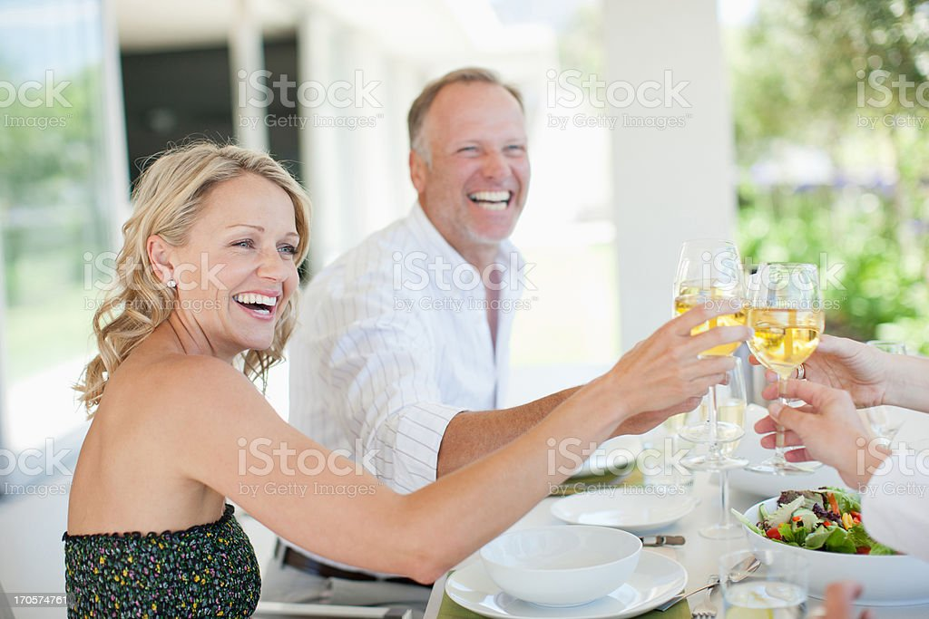 Friends making toast with wine glasses stock photo