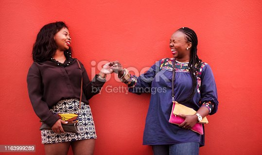 Shot of two female friends meeting against red background