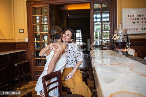 Two fashionable friends meeting after long time in bar, kissing and embracing