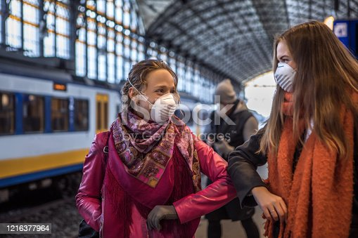 Friends, wearing protective masks, meeting in a public transport hub using an alternative handshake during corona virus outbreak