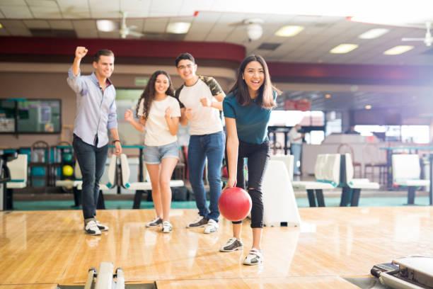 vrienden motiveren tiener meisje bowling bal te gooien op alley - bowlen stockfoto's en -beelden
