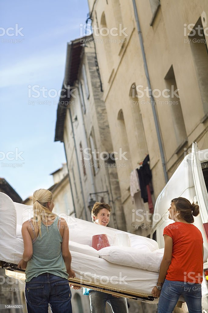 Friends move couch in street stock photo