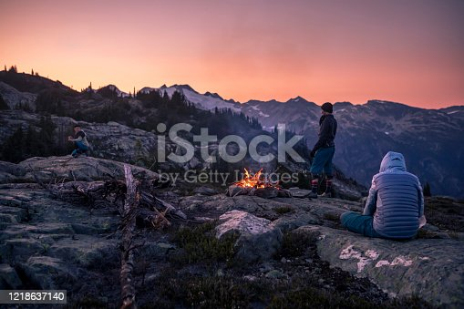 Group of friends enjoying fire while camping outdoors, in an alpine wilderness near Whistler, BC, Canada.