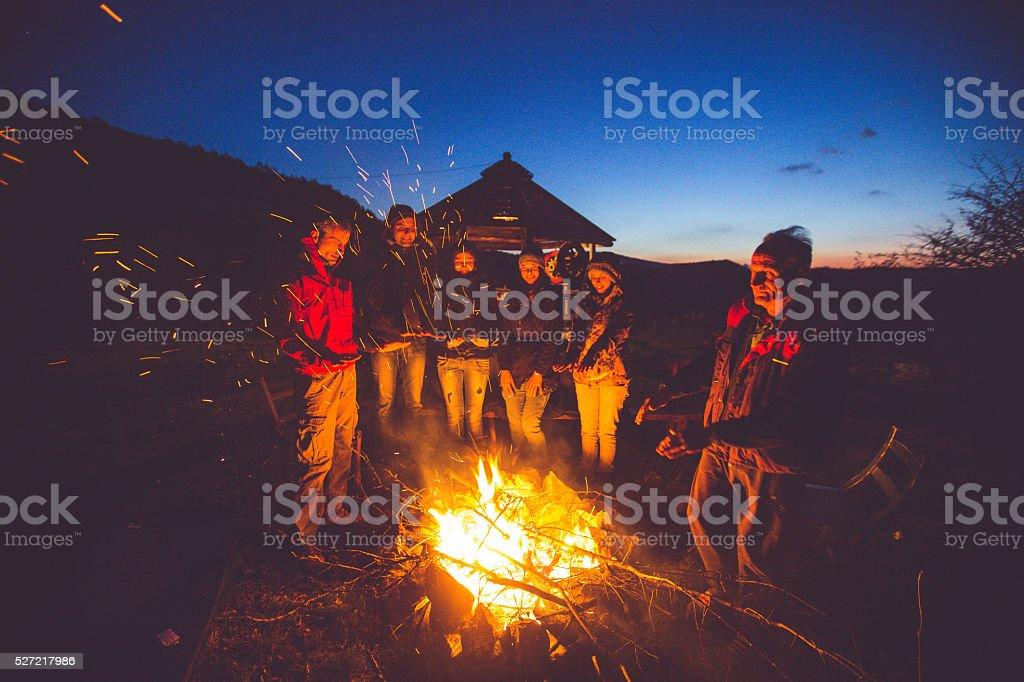 Friends near campfire stock photo