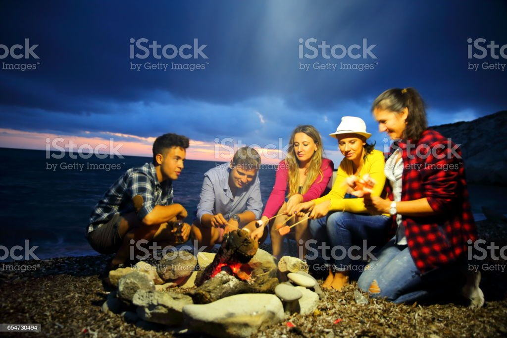 Friends near campfire stock photo