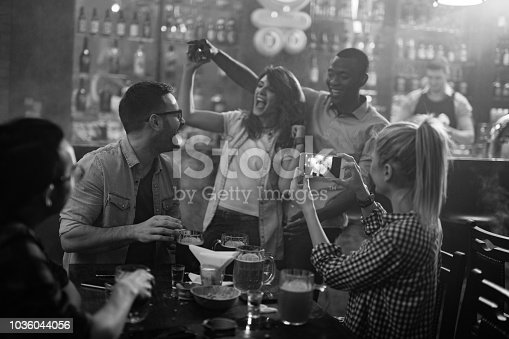 Group of cheerful friends having fun while dancing in a bar. Black and white.